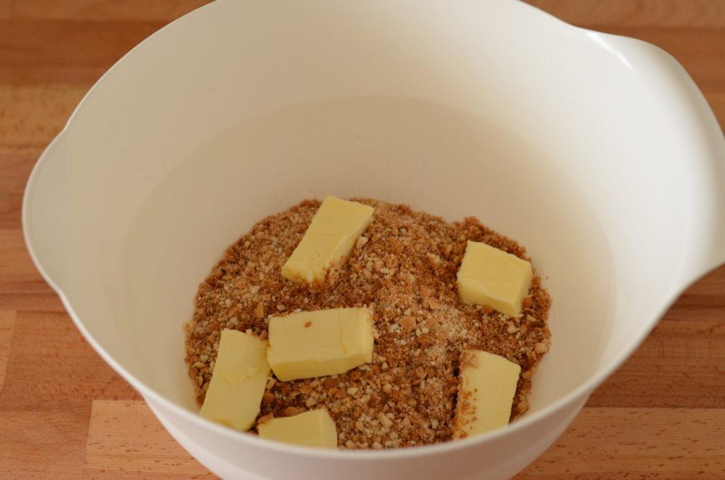 k rozdrceným sušenkám přidáme máslo a prsty propracujeme