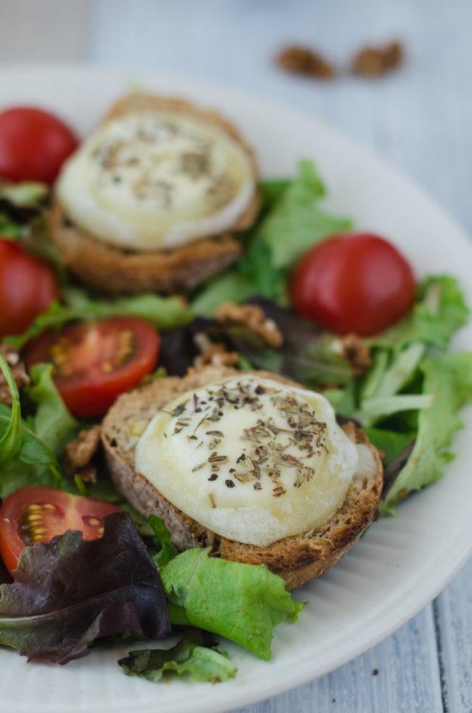 Salát s rozpečeným kozím sýrem jak ho dělám já, to jsou malé toastíky s plísňovým kozím sýrem zakápnutým medem a provensálskými bylinkami na chvilku rozpečenými v troubě, naaranžované na lůžku ze směsi salátových listů, cherry rajčátek a vlašských ořechů s medovou zálivkou.
