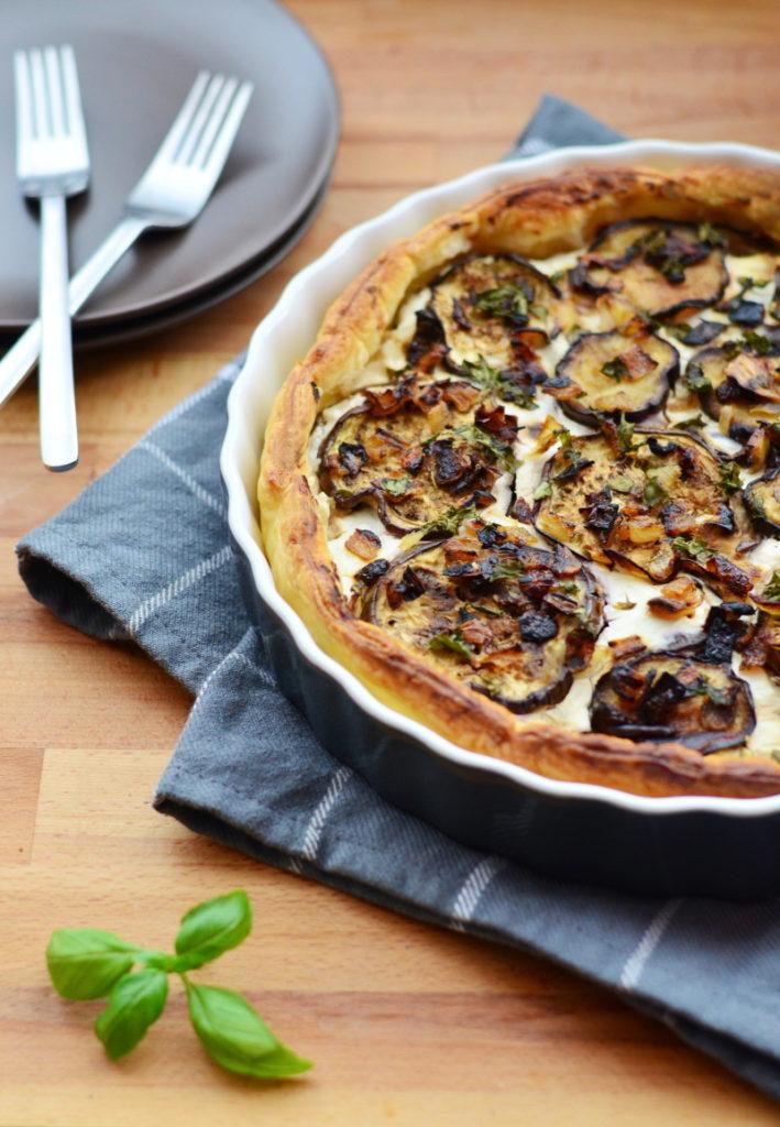 Tento vynikající lilkový quiche s kozím sýrem je vlastně takový slaný koláč s orestovaným lilkem a cibulkou, čerstvým kozím sýrem a bazalkou.