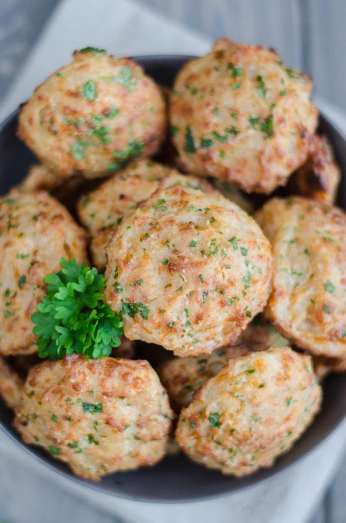 Měkkounké čedarové sušenky s toppingem z rozpuštěného másla, petržele a granulovaného česneku jsou v USA velice oblíbené jako Cheddar Bay Biscuits.