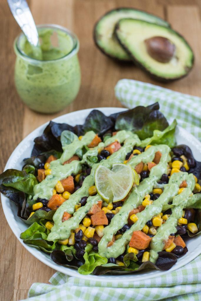 Salát s pečenými batáty, fazolemi a kukuřicí je moc dobrý kompletní salát. Avokádovo-jogurtový dressing s koriandrem a česnekem mu dodá fantastickou chuť.