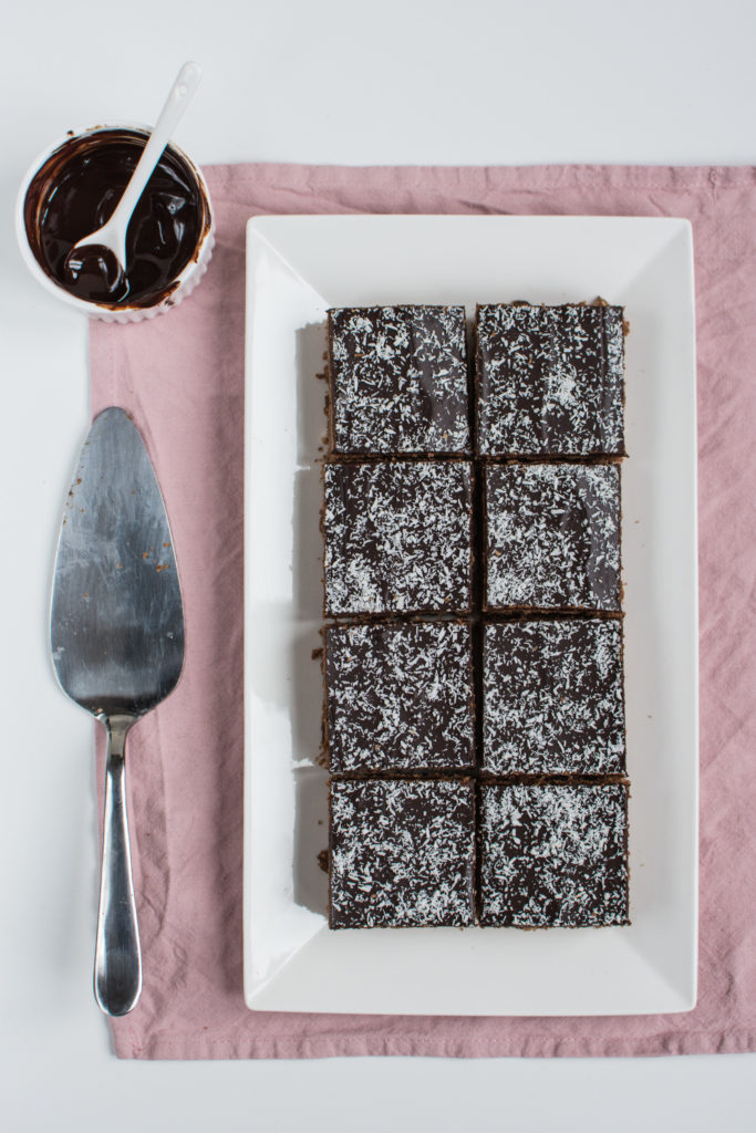Recipe for a delicious Czech Spice Cake (perník) - a simple sheet cake with a mix of spices, coconut and plum jam, covered with melted chocolate.